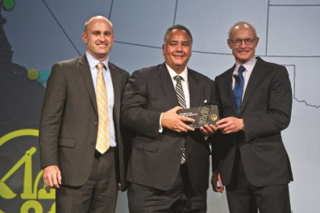 Gary Johnson (center) accepts the award recognizing American Flooring & Interiors contractors at the annual ICIC awards. Also pictured are: Michael Porter (left), ICIC founder and Harvard University professor and Matt Camp (right), ICIC president and COO.