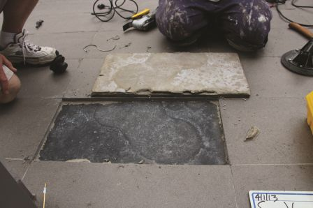 Tile was detached, removed. Roof waterproof membrane did not meet ANSI A118.10.