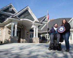 Pictured in front of their new home are Police Officer Michael Flamion and his wife, Sarah.