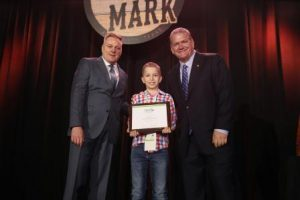 Finneas Luca accepts NWFA Next Generation Award from Michael Martin and Chris Zizza