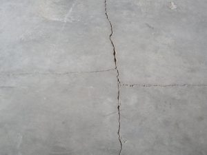 When the control joints are too far apart or there are no joints at all the concrete will develop its own joints. These cracks usually will quarter the slab between other joints.