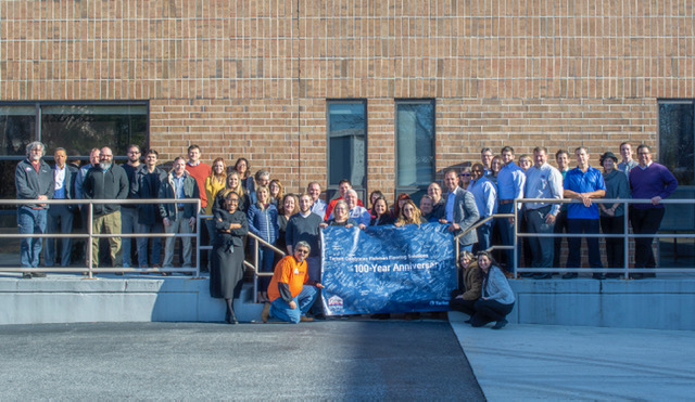 Employees from Tarkett and Fishman Flooring Solutions proudly display the banner celebrating Fishman's 100 years of business success.