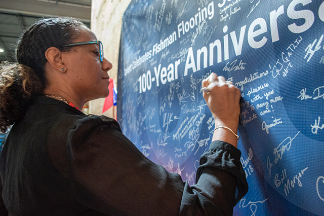 Fishman's Nicole Robinson adds her signature to the celebratory banner, which will be on permanent display at Fishman's Baltimore headquarters.